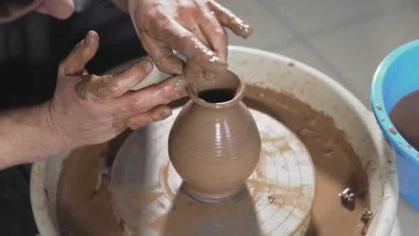 Sculptor in workshop makes jug. Hands create product from clay