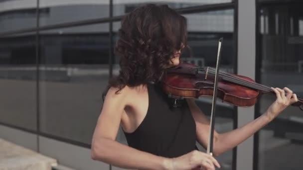 Közelről elegáns nő fekete ruhában, hegedű közelében üvegház
