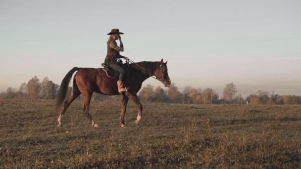 junges Cowgirl auf braunem Pferd in Zeitlupe im Freien. schöne Frau reitet Pferd
