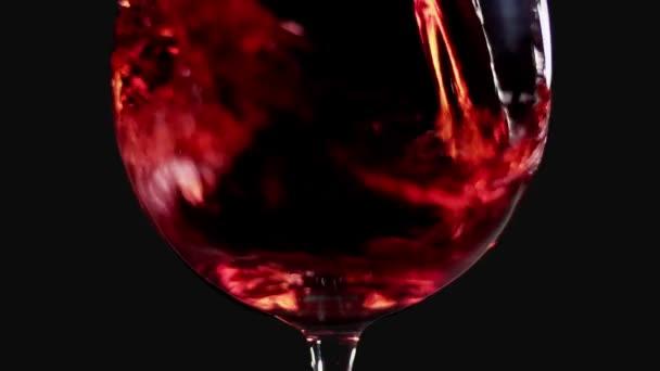 Naplnění sklenice na víno s červeným vínem super zpomaleně makro snímek, černé pozadí