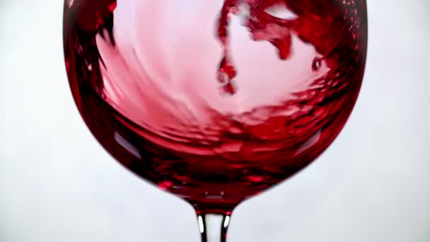 Filling glass with red wine super slow motion macro shot on white background