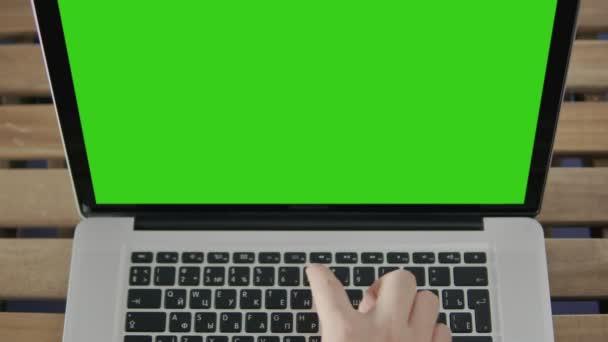 Hand eines Mannes, der am Laptop arbeitet und auf der Tastatur tippt. Green Screen aus nächster Nähe