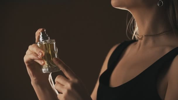 Sensual girl spraying fragrance in slow motion, with scent particles