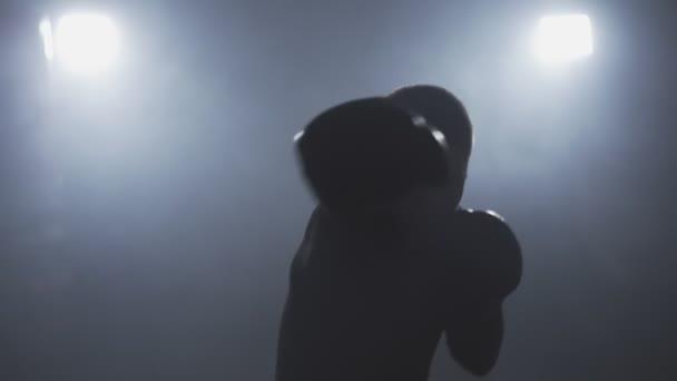muay thai Kämpfer boxt und schaut in die Kamera. Kickboxtraining