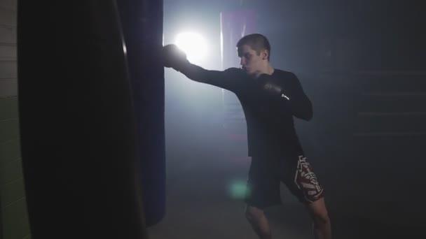 Kickboxer-Training mit Boxsack. Muay thai Kämpfer Stünzen in rauchiges Studio