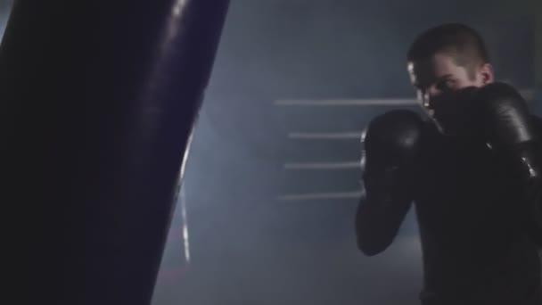 Kickboxer in rauchigen Studio Stanzen. Muay thai Kämpfer mit Boxsack training