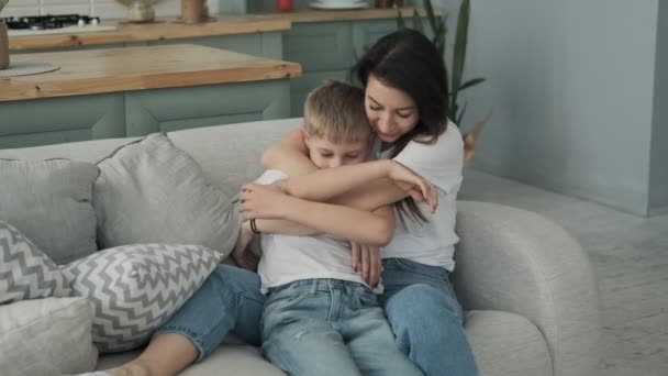 Šťastná rodina tráví čas společně v hraní a objetí. Mladá matka a syn se baví na pohovce v obývacím pokoji