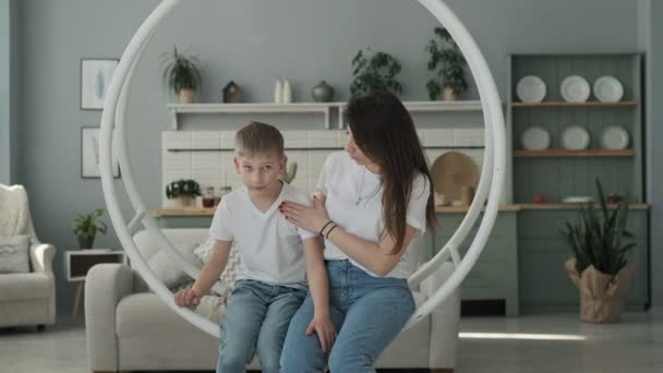 Young mother and son having fun on swing in living room. Happy family spending time together, playing and hugging.
