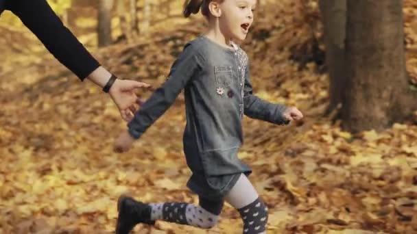 Daughter run away from mom in autumn park. Family having fun outdoor in slow motion. Happy family concept. Medium shot