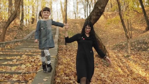 Young mother and her happy daughter walking together on stairs in autumn park