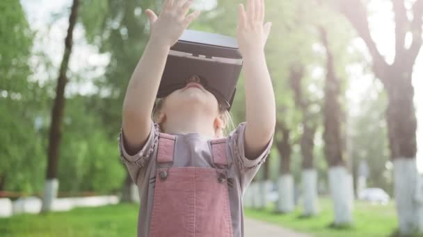 Children in pink sundress wearing virtual reality glasses with fun and surprising face standing outdoor. Little caucasian girl 4-5 years using VR glasses headset on nature. Medium shot