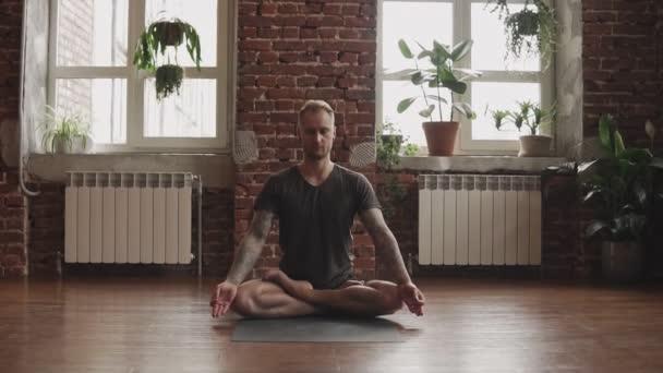 Mladý muž dělá jógu v lotosu pózuje ve studiu s dřevěnou podlahou a velkými okny. Muž cvičí jógu uvnitř. Svoboda, zdraví a koncepce jógy. Snímek fotoaparátu nahoru