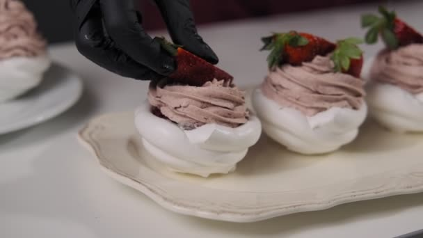 Decorating cake with strawberry. Butter cream on tasty desserts of Pavlova. Close up of home bakery concept