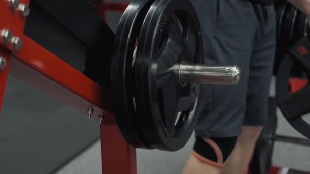Close up of bodybuilder prepare to do exercises with barbell in gym, keep barbell plate in hands in slow motion
