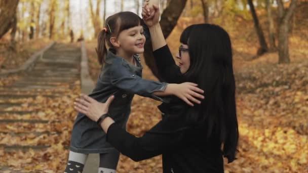 Glückliche junge Mutter und ihre kleine Tochter spielen, umarmen und lachen im Herbstpark. Familienglück. mittlerer Schuss