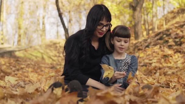 Matka a dcera si hrají s podzimní listkou. Máma seděla na zemi a objala dceru. Rodina se baví v podzimním parku v pomalém pohybu. Šťastný rodinný koncept. Střední záběr