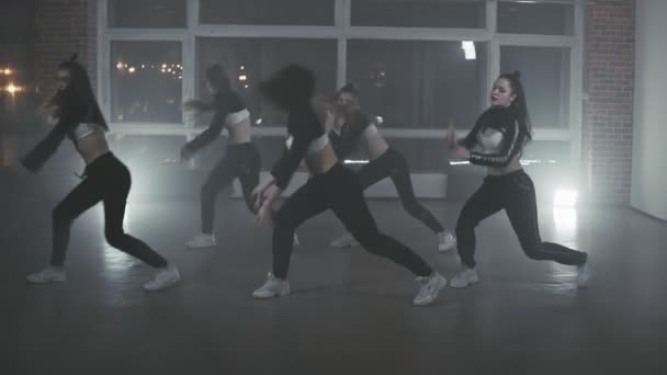 Hip-hop dancers performing on the stage. Happy dancing women. Girls enjoying funky hip hop moves in dark studio with smoke and lighting