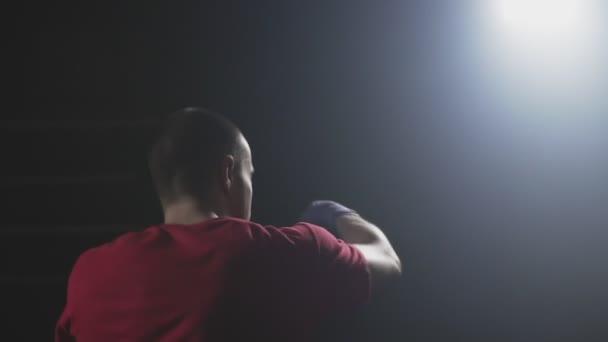 Muay thai Kämpfer training in rauchigen Atelier in Zeitlupe. Kickboxer Stanzen. Silhouette auf dunklem Hintergrund