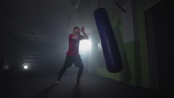 Kickboxer boxen im verrauchten Studio. Muay Thai Kämpfer Training mit Boxsack auf dunklem Hintergrund