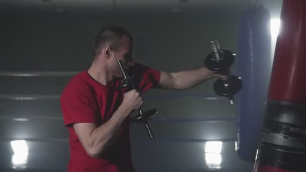Figher training with dumbbells in smoky studio. Kickboxer training punches in low light gym in slow motion. Silhouette on dark background. Weight in hands