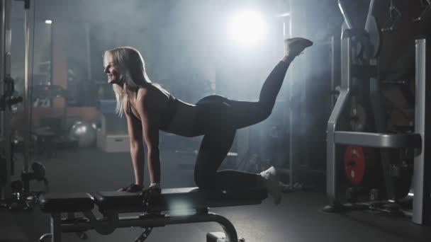 Schöne Mädchen tun Kick Backs auf der Bank in dunklen rauchigen Fitness-Studio in Zeitlupe. Gesunder Lebensstil. Sexy blonde Frau Training im Sportzentrum. Porträt in voller Länge