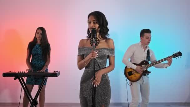 Stílusos lány énekel mikrofonnal. Közepes shot vonzó női énekes ruhában. Zenészek a rock zenekar a stúdióban játszik dalokat színes fények a háttérben