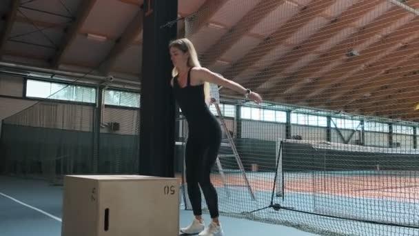 Athletische Frau macht Box Sprünge in Innenräumen. Junge starke Hündin mit perfektem Fitness-Körper in Sportbekleidung tun Satz von Box Sprünge im Fitnessstudio in Zeitlupe. Vollwertiger Schuss