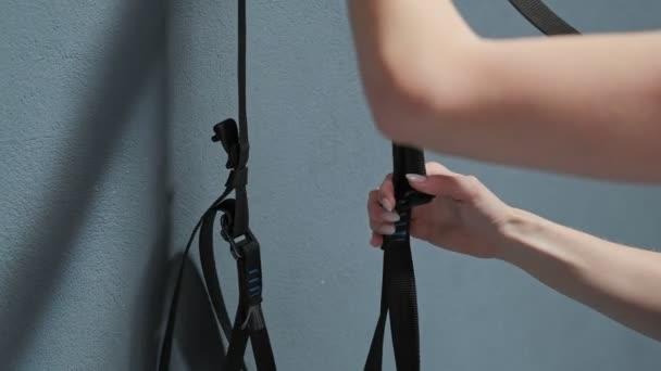 Nahaufnahme der fit schönen Frau immer bereit Fitness-Riemen für Trx Übung. Junge blonde frau im Fitness-Studio