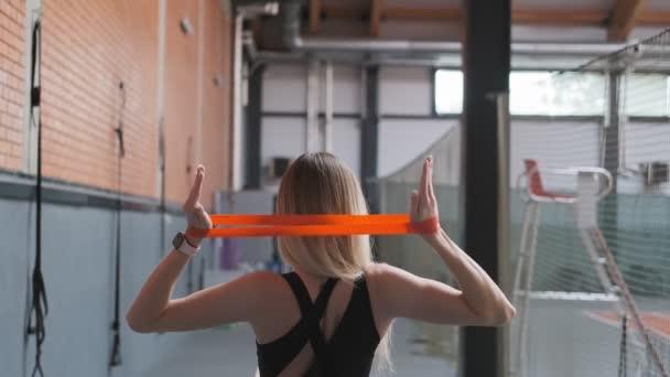 Krásná žena ve sportovně se cvičením s elastickou kapelou v ruce. Střední záběr ženy v tělocvičně. Záda atraktivní blondýnka