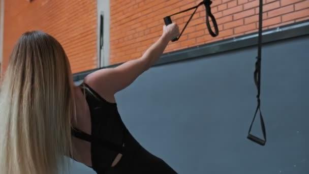 Athlet junge Frau tun Pull-ups mit trx Fitness-Riemen im Fitness-Studio. Nahaufnahme der Fitness-Frauen, die Bewegung in Innenräumen. Training im Fitnessstudio