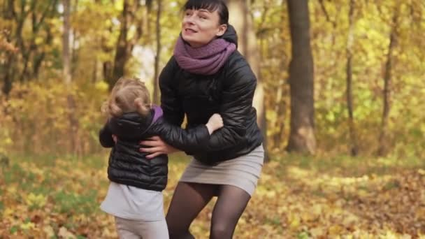 Little daughter in mothers hands in autumn park. Daughter and young mother having fun outdoors