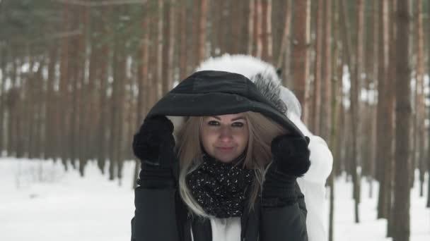 Šťastný pár se baví v lese se sněhem. Šťastní mladí lidé hází sníh přes hlavu. Zimní zábava v pomalém pohybu.