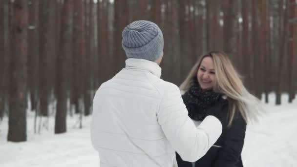 Paar auf einem Spaziergang im Winterpark. Schöne Frau und Mann umarmen und lächeln im Freien in Zeitlupe.