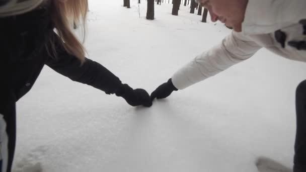 Schönes Paar haben Spaß im Freien. Mann und Frau ziehen Herz auf Schnee