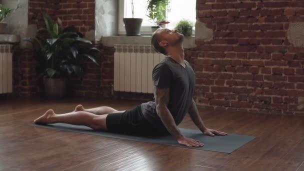 Yogi Master Workout auf schwarzer Matte im urbanen Studio. Junger Mann praktiziert Yoga