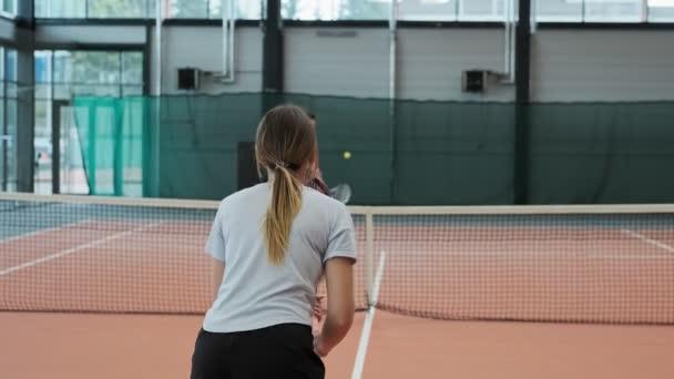 Sportovní žena v modrém tričku, hraje tenis vevnitř. Žena v sportovním oblečení hraje tenis ve zpomaleném pohybu. Střední záběr hráče. Sportovní koncepce