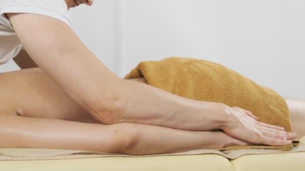 Nő élvezi testmasszázs a Spa klubban. Közeli fel a terápiás masszázs. Testápolás és bőrápolás
