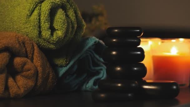 Farben Handtücher, heiße Steine und Kerzen für entspannende Wellness-Massage und Körperbehandlung. schöne Komposition mit Kerzen und heißen Steinen. Spa- und Wellness-Konzept mit Umgebungslicht
