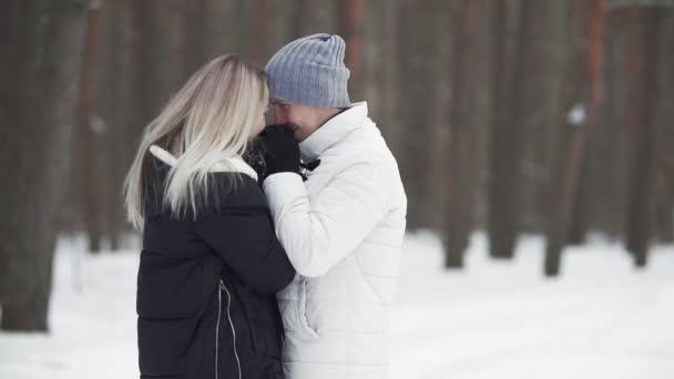 Krásná žena a muž se s pomalým pohybem usmívají venku. Pár na procházku v zimním lese s prostorem pro kopírování