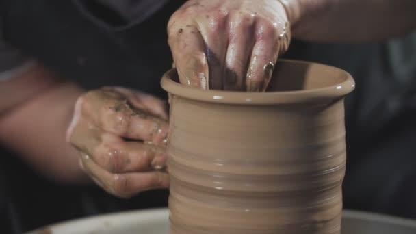 Nahaufnahme eines Töpfers, der mit Ton auf der Töpferscheibe arbeitet. Mann kreiert Krug aus Ton in Zeitlupe.
