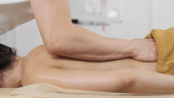 Frau mit Massage. junge schlanke Frau erhält Verjüngungskur im Kurort.