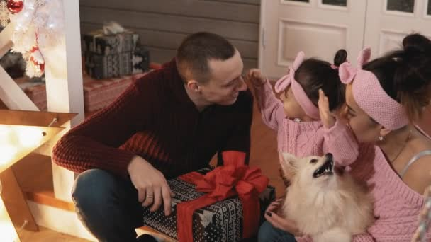 Young family in pullovers hugging in Christmas day. Happy family concept. Medium shot. Smiling family with little daughter and dog having fun together.