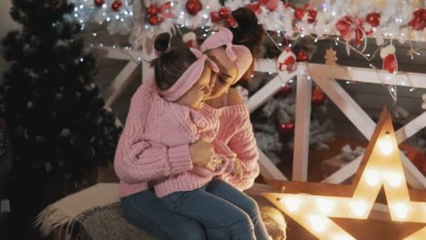 glückliche Mutter, die Spaß mit ihrer kleinen Tochter in der Nähe des Weihnachtsbaums hat. schöne Mutter und Tochter in rosa Pullovern. Mutter kitzelt ihre kleine Tochter in Zeitlupe. Mutterschaftskonzept. mittlerer Schuss