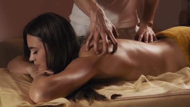 schöne junge Frau mit Massage für die Schultern im Wellnessbereich bei Umgebungslicht. Mittlere Aufnahme der Körpermassage. Männliche Hände massieren die Frau auf dem Massagetisch in Zeitlupe. 4k, uhd