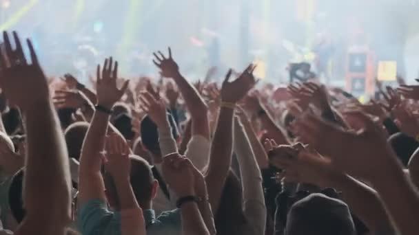 Šťastní lidé sledují úžasný hudební koncert. Fanoušci zdvihněte ruce a fotí mobilní telefon. 4k, UHD