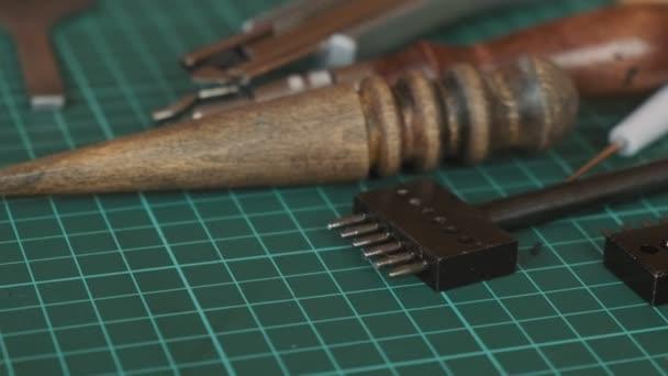 Nástroje pro kožený vzor na stole. Příslušenství pro ručně vyráběné díly. Práce řemeslníka v dílně