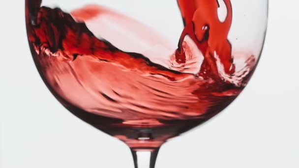 Pomalý pohyb vína z láhve do mixu. Zblízka na červené víno tvoří krásnou vlnu ve skle. Víno ve skle na bílém pozadí.