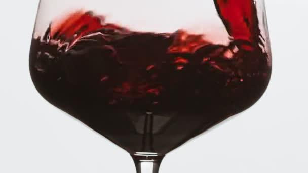 Cu sommelier nalévá výborné červené víno ve skle. Růžové víno nalije do skleničky. Uzavření plnící skleničky vína s červeným vínem super pomalý pohyb. Makro na bílém pozadí