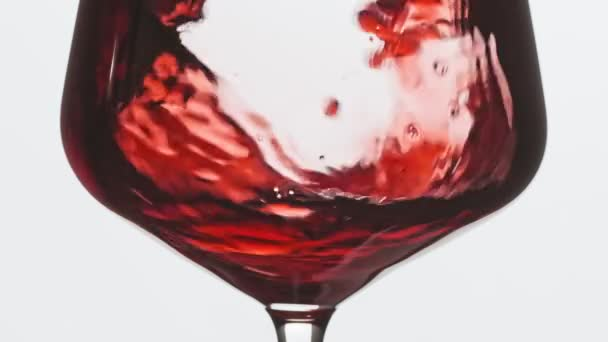 Pouring red wine into goblet. Close-up of filling wine glass with red wine in super slow motion. Red wine forms beautiful wave in glass