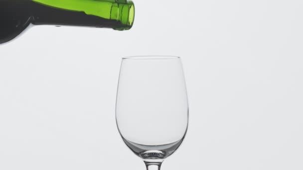 A palackból felömlött Rózsa bor. Sommelier ömlött kiváló vörösbor üvegből. Közelképek a borpohár feltöltéséhez vörösborral, lassú mozgásban. Központi összetétel.